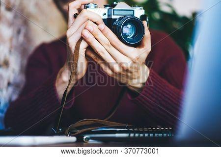 Selective Focus On Mans Hands Holding Vintage Camera With Modern Lense.