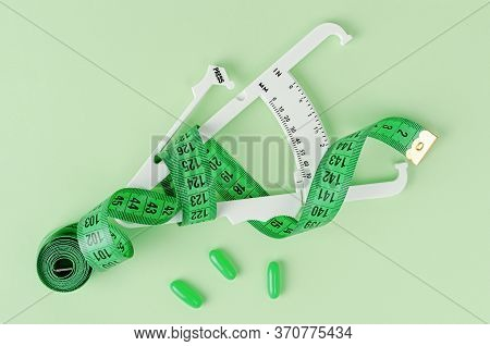 Weight Loss Concept. Measuring Tape, Pills And Caliper On Green Background. Top View.