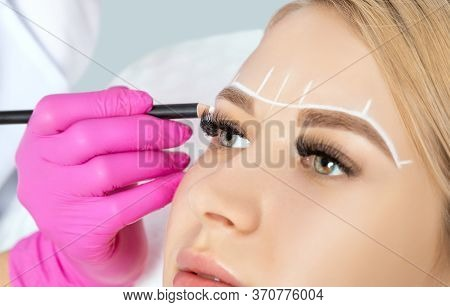 Woman Having Permanent Make-up Tattoo On Her Eyebrows.permanent Make-up For Eyebrows In Beauty Salon