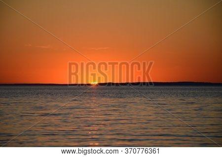 Bright Sunset Over The Lake. Red-orange Sunset. Dark Water. The Sun Sets Over The Horizon.