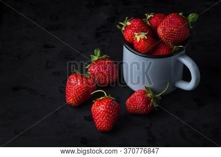 Strawberries On A Black Background. Enamel Mug Full Of Strawberries. Several Strawberries Lie Nearby