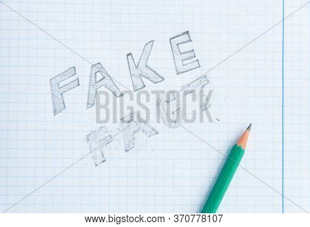 Fake News Concept. Fake - Fact. Drawing In A Notebook And Pencil. Erased Word Fact. Fake Information