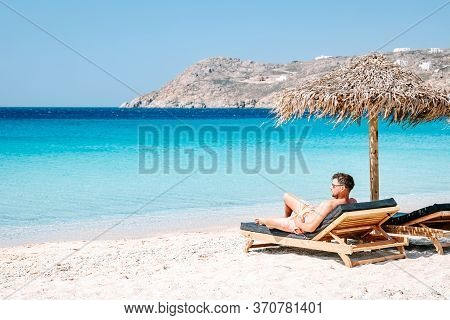 Young Guy In Swim Short At The Beach Of Mykonos Greece, Guy At Beach Chair On The Mykonos Beach