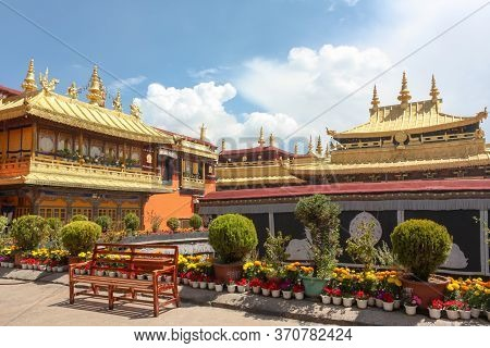 Jokhang Temple Gplden Roof In Lhasa, Tibet From Distance With A Bench