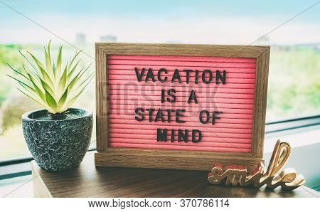 Vacation is a state of mind positive inspirational quote text on message board for summer holidays travel plans cancelled due to COVID-19 coronavirus. Staycation pink felt board text for staying home.