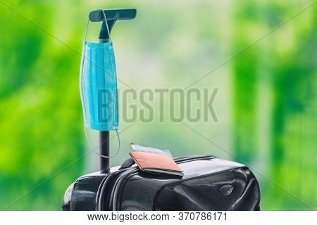 Summer travel during coronavirus face mask obligatory wearing in airport and airplane during flight with passport, suitcase, plane ticket.