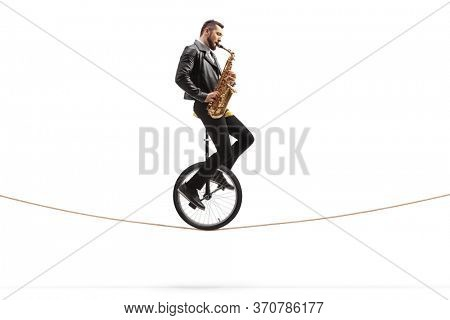 Musician riding a unicycle on a rope and playing a saxophone isolated on white background