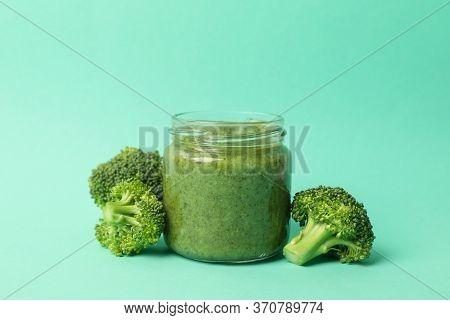 Glass Jar With Broccoli Puree On Mint Background