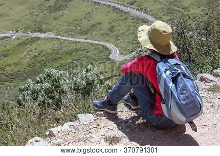 Hiking Trail Around Drepung Monastery Near Lhasa With A Tourist Woman Wearing A Hat Sitting And Look