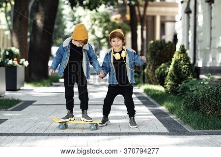 Two Adorable Twin Boys Play With Skateboard Or Pennyboard With Happy Faces In The Street.