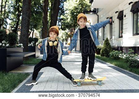 Two Gleeful Twin Boys Play With Skateboard Or Pennyboard In The Street.