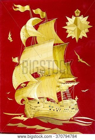 A Large Beautiful Three-masted Sailing Ship Frigate Made Of Yellow Straw On A Red Velvet Background.