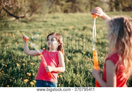 Funny Hilarious Moment. Girls Friends Blowing Soap Bubbles In Park On Summer Day. Kids Having Fun Ou