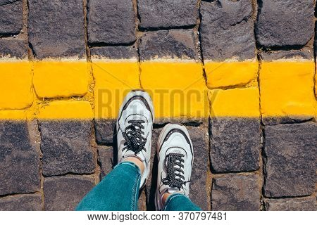 Women's Feet In White Sneakers Stand On The Pavement One Foot Stepped On A Bright Yellow Line, Cross
