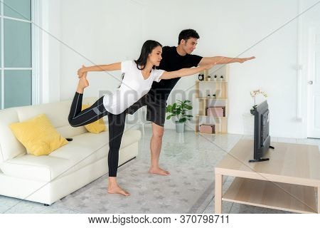 Young Asian Couple Doing Yoga Practice Together And Looking Tv At Home, Man And Woman Working Out To