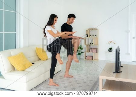 Young Asian Couple Doing High-intensity Interval Training Together And Looking Tv At Home, Man And W