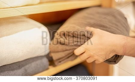 Male Hand Choosing Sheet Of Fabric Or Textile. Group Of Multi-colored Earth Tone Fabric Swatch For B