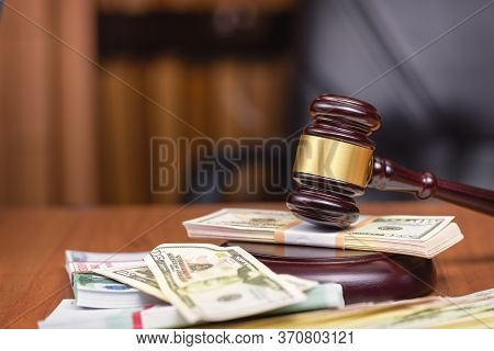 Corrupt Court.trial Of Money Scammers. Judges Gavel And Bundles Of Money On The Judges Table.