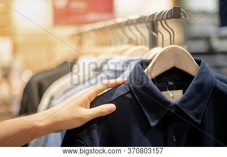 Male Hand Choosing Clothes For Checked Pattern Cotton Polo Shirt On The Rack In Cloth Shop At Depart