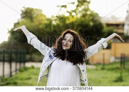 Beautiful Young Brunette Woman In A White Dress And Denim Jacket Smiling, Arms Outstretched Against