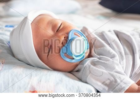 Infant Newborn Baby Boy Sleeping Peacefully With Pacifier On The Bed