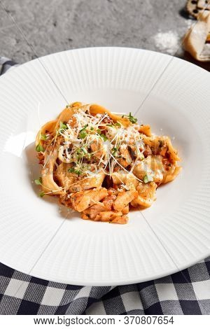 Pappardelle pasta with salmon and sauce bisque served in white plate. Traditional Italian dishes with decorative tartan cloth