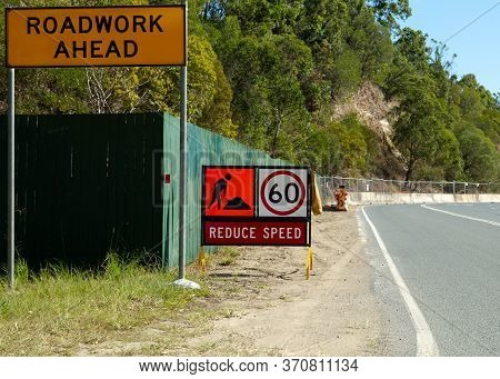 Roadwork Ahead Reduce Speed Signage On A Suburban Road