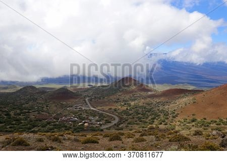 Scenic Mauna Kea Landscape With Paved Road To Summit Between Old Craters And View On Mauna Loa In Cl