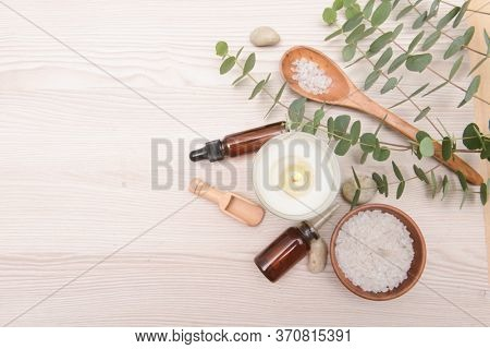Eucalyptus leaves and candle , bottles of essential oil ,stones,salt in spoon bowl,candle on wooden background