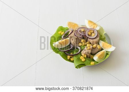 Canned Tuna With Eggs, Suggar Corn, Red Onion Rings On Green Lettuce Leaf, Slice Of Lemon In Pocelai