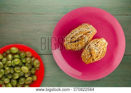 Cakes With Sesame Seeds On A Pink Plate With Fruits Top View. Cakes With Sesame Seeds On A Green Woo