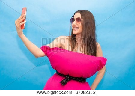 Happy Woman In Pink Pillow Dress And Sunglasses Making Selfie Photo On Mobile Phone For Crazy Pillow