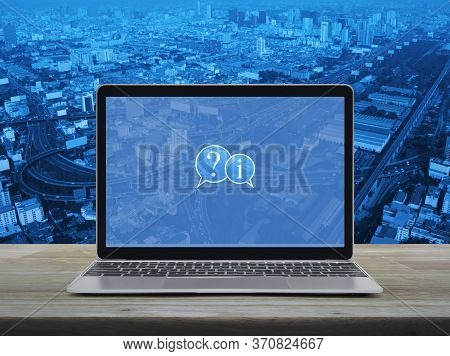 Question Mark And Information Chat Icon With Modern Laptop Computer On Wooden Table Over City Tower,