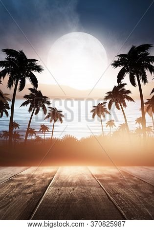 Tropical Sunset With Palm Trees And Sea. Silhouettes Of Palm Trees On The Beach Against The Sky With