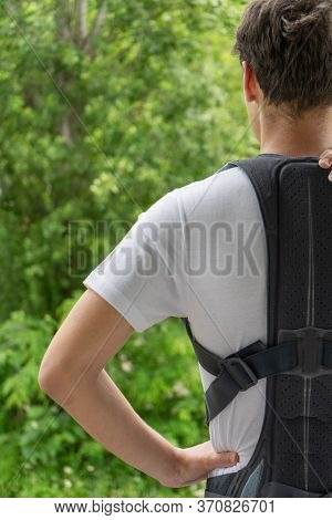A Teenager Wearing A Lumbar Corset, Rear View. Corset To Support The Back. Correction Of Posture In