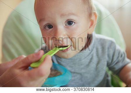 Closeup Cute Little Baby Eating Tasty Porridge Milk. Mother Hand With Spoon. Mom Feeding Son. Boy Si