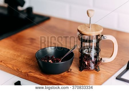 Loose Hibiscus Tea In French Press. Bright Kitchen Interior. Wooden Complete Kitchen With Gas Oven.