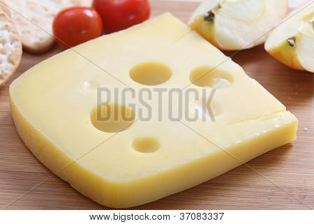 A wedge of Jarlsberg Danish cheese with crackers and cherry tomatoes on a cheeseboard