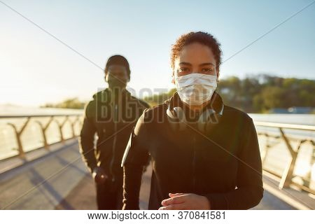 Jogging During Quarantine. Young African Couple Wearing Face Medical Masks While Running Together On