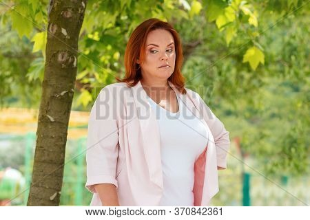 Emotions. Portrait Of A Plus-size Woman Showing Her Frustration And Discontent. In The Background Gr