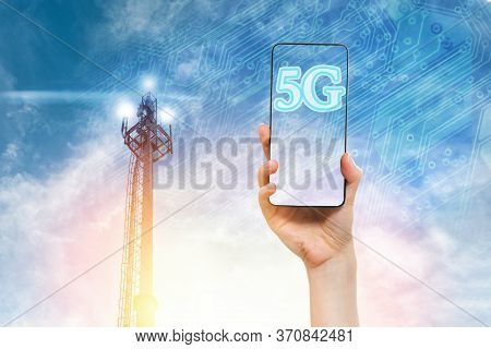 A Womans Hand Holds A Smartphone Against A Blue Sky With A 5g Telecommunications Tower. Concept Of M