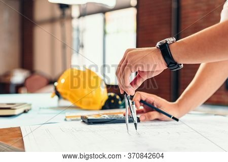 Architect Using Divider Compass Working On Blueprint. Blueprints, Ruler, Calculator, Safety Hat And