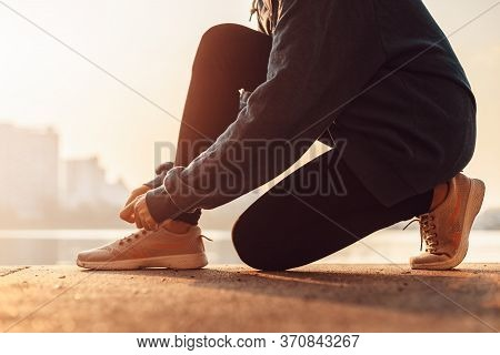 Woman Tying Shoe Laces In The Morming.