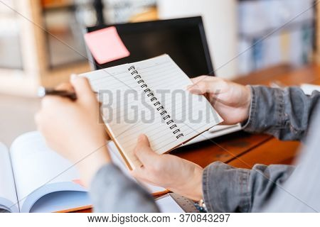 High School Or College Students  Group Catching Up Workbook And Learning Tutoring On Desk And Readin