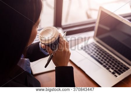 Businesswomen Drink Hot Coffee Between Working. Laptop, Calculator And Paper On The Table.