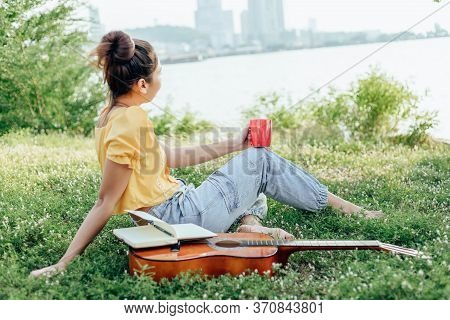 Hands Hold Coffee Cup And Write Notes,lyrics In The Book On Quitar Beside The Sea And Building City