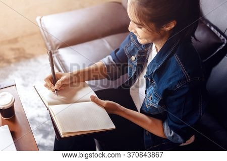 Businesswoman Writing A Note In Notebook At Coffee Shop.