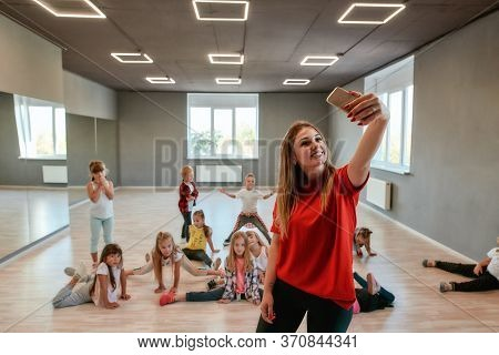 Young And Positive Dance Teacher Making A Selfie With Children While Having Choreography Class. Danc