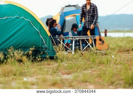 A Group Of Friends Traveling And Camping Near Lake And Mountain Back.