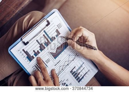 Businessman Hold Pen And Working Calculate Data. Document Graph Chart And Report Marketing. Business